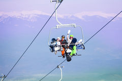 Three snowboarders sit on ropeway in mountains Royalty Free Stock Photos