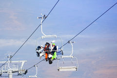 Three snowboarders sitting on ropeway Stock Photography
