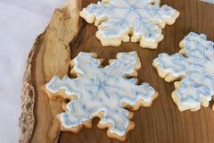 Three snowflake cookies. Three iced snowflake cookies on wooden board Stock Photos