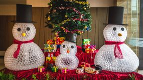 Three snowman as Christmas decoration. Three snowman made from used mineral water plastic glasses and other Christmas decoration at hotel lobby Stock Images