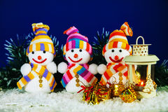Three snowman with a lantern Royalty Free Stock Photography