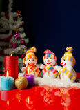 Three snowmen and burning candles Royalty Free Stock Photo