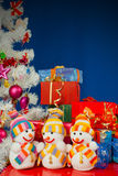 Three snowmen in front of the Christmas presents. Over the blue background Stock Images