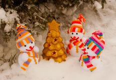 Three snowmen with golden evergreen tree Royalty Free Stock Images