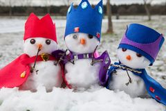 Three snowmen kings dressed with crowns and capes. Three cute king snowmen dressed with crowns and capes looking very regal. Snow fall background in a rural Royalty Free Stock Photos