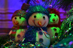 Three snowmen. Toy Snowmen under this Christmas tree on New Year's night under the light of lights stock images