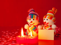 Three snowmen with two burning candles Stock Photo