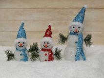 Three merry snowmen on fluffy snow Royalty Free Stock Photos