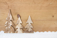 Three snowy Christmas trees on wooden background Stock Photo