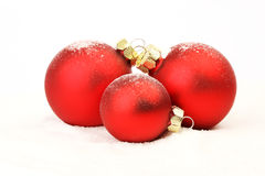 Three snowy red christmas matt balls standing on snow on white background Stock Photo