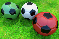 Three soccer balls on grass Royalty Free Stock Images
