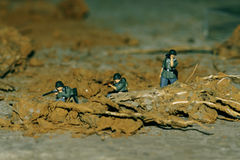 Three soldiers are ambushing in battlefield. Three miniature soldiers are ambushing under the trench Stock Images