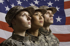 Three soldiers posed in front of American flag, horizontal royalty free stock image
