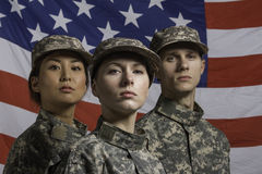 Three soldiers posed in front of American flag, horizontal Stock Photography