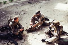 Three soldiers are sitting on tires and having rest. They had a good fight. Men want to keep their strenght for the next. Fight. One of them is holding firls Stock Photos