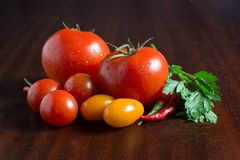 Three sorts of tomatoes, red, yellow and cherry on a wood table with parsley leaves. stock images