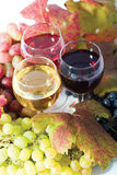Three sorts of wine. In glasses - red, rose and white and grapes Stock Image