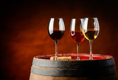 Three sorts of wine. On a barrel in a winery. red, rose and white wine Royalty Free Stock Photos