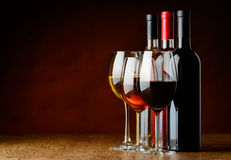 Three sorts of wine. Red, white and rose wine in wineglass and bottle on wooden table Stock Image