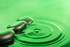 Three spa stone drops lie in the green water Stock Image