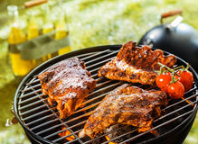 Three spicy racks of rib cooking on a BBQ fire Royalty Free Stock Image