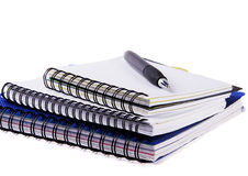 Three spiral notebooks and pen Royalty Free Stock Photography
