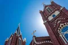 Three spires with white crosses against blue sky, Gothic Revival church. Horizontal aspect stock photo