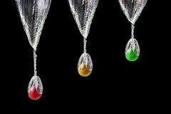 Three splashing fruits. Three frutis falling on water isolated on black background Royalty Free Stock Images