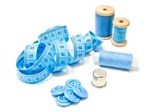 Three spools of blue thread, buttons and meter. Three spools of thread, buttons and meter on white background Royalty Free Stock Images