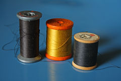 Three spools of thread on blue background Royalty Free Stock Image
