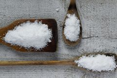 Three spoons with salt on wooden background Stock Photos