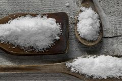 Three spoons with salt on wooden background Stock Photography