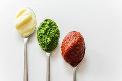 Free Three Spoons With Different Condiments - Mayonnaise, Tomato Sauce And Pesto Stock Photos - 104193183