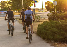 Three sport Man riding a bike. In the city at sunset Royalty Free Stock Photo