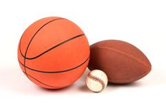 Three sports. The 3 major sports in the United States represented by the balls used to play them: football, basketball and baseball Stock Image