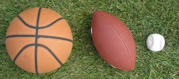 Three Sports. A basketball, football, and baseball rest on the grass stock images