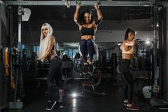 Three sports women bodybuilders intensively training on the horizontal bar and block simulator. Biceps and triceps. Extension royalty free stock photo