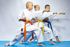 Three sportsmen are beating blows arms on a blue mats Royalty Free Stock Photos