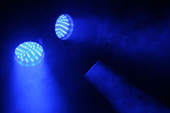 Three spotlights shine with blue light. In the dark Stock Photo
