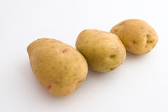 Three spuds. Oblong form, close-up, located diagonally frame, on light background Stock Images