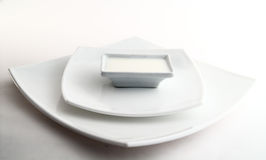 Three square white plates with milk Stock Photos