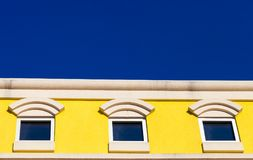 Three square windows on a yellow building with bright blue sky i royalty free stock images