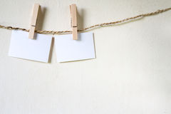 Three squares of blank paper, pegged to a string washing line. With wood plank fence in the background royalty free stock photos