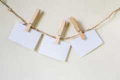 Three squares of blank paper, pegged to a string washing line. With wood plank fence in the background Stock Images