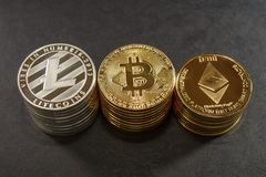 Three stack of cryptocurrency coins. Bitcoin, litecoin and ethereum Stock Photos