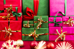 Three Stacks of Xmas Presents Arranged by Color. Three heaps of wrapped gifts sorted by color. Red, green and magenta. All plain-colored with monochrome ribbons Stock Photo