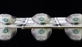 Three stainlees steel spoon and US dollar banknotes Stock Images
