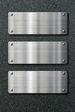 Three stainless steel metal plates on black Stock Image