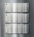 Three stainless steel metal plates on brushed Royalty Free Stock Images