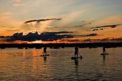 Three stand-up paddler at Lake Starnberg, Bavaria, at sunset.  Stock Photography